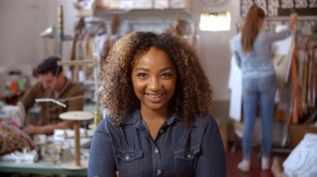 Mixed race woman in design studio walks in to focal plane Stok Video