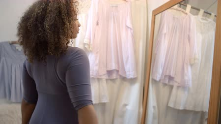 nativo americano : Woman trying on a dress in a boutique changing room Stock Footage