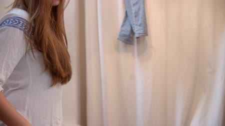 brim : Woman trying on jeans in changing room, side view, tilt shot Stock Footage