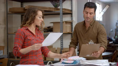 post room : Manager and colleague discuss a clothing order for dispatch Stock Footage