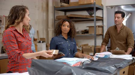 colegas de trabalho : Team packing clothing orders for distribution Stock Footage