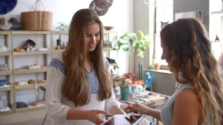 each other : Woman paying shop assistant with credit card in a boutique Stock Footage