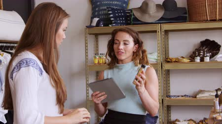 butik : Shop assistant talks to a customer and shows her products, shot on R3D Stok Video