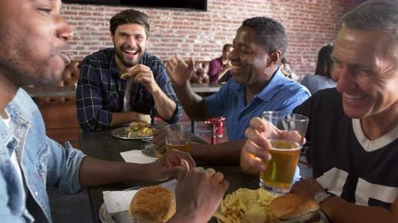 fries : Group Of Male Friends Eating Out In Sports Bar Shot On R3D Stock Footage