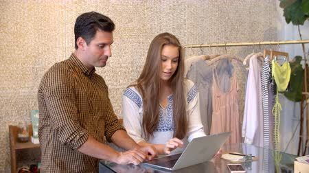 butik : Male manager trains young woman using laptop in clothes shop