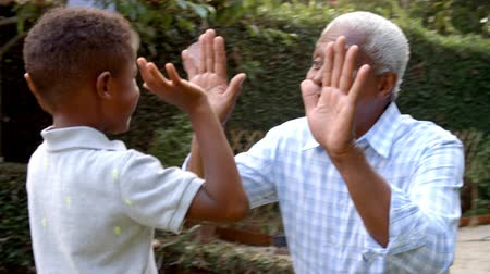 each other : Young black boy playing clapping game with grandad in garden
