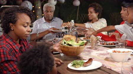 reaching : Multi generation black family serving food at table outdoors Stock Footage