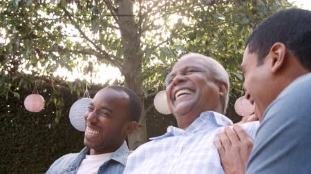 socialising : Black dad and two adult sons laughing together in garden