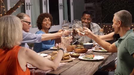 socializing : Group Of Mature Friends Enjoying Outdoor Meal In Backyard