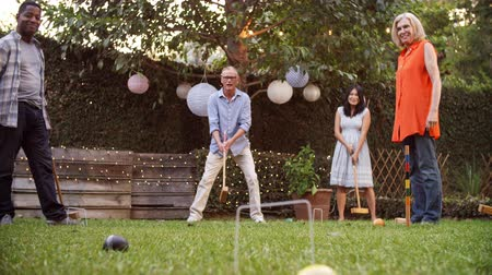 vietnami : Group Of Mature Friends Playing Croquet In Backyard Together Stock mozgókép