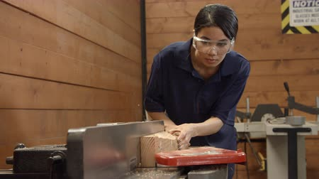közepes : Female Carpenter Using Plane In Woodworking Woodshop Stock mozgókép