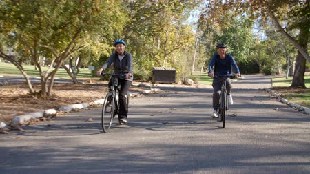 ciclismo : Senior Couple Cycling Through Park In Slow Motion