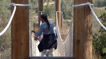 etnia africano : Multi generation black family crossing rope bridge, back view Stock Footage