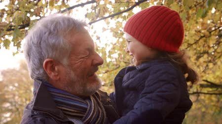 woodland : Grandfather Walking With Granddaughter In Autumn Countryside