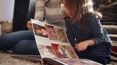 выстрел : Mother And Daughter At Home Looking Through Photo Album