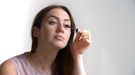 getting ready : Studio Shot Of Attractive Woman Putting On Mascara