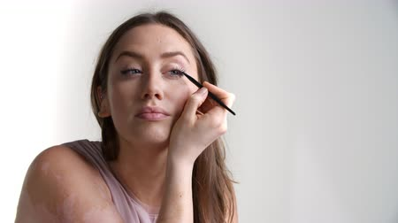 getting ready : Studio Shot Of Attractive Woman Putting On Eyeliner