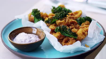 kalmar : Plate of fried squid, kale and sumac mayo pulls out of focus