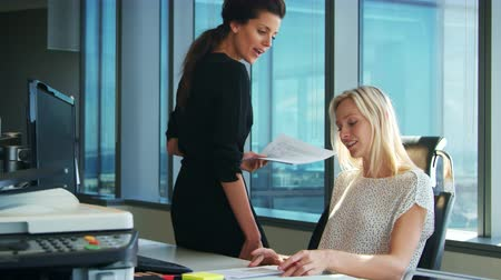 встреча : Two Businesswomen Working At Desk Discuss Document