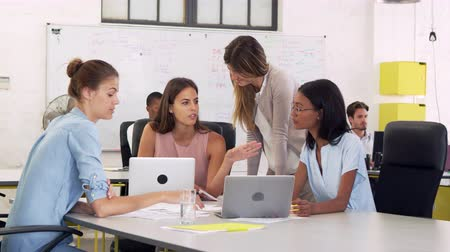 each other : Four young businesswomen working at desk in open plan office Stock Footage