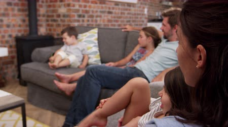 family watching tv : Family Sit On Sofa In Open Plan Lounge Watching Television Stock Footage