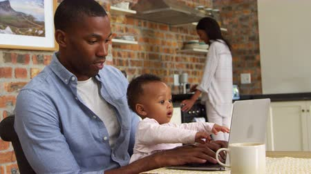 focus on foreground : Father And Baby Daughter Use Laptop As Mother Prepares Meal