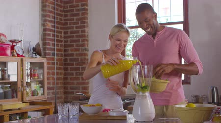 kitchen blender : Mixed race couple making smoothies together at home, shot on R3D
