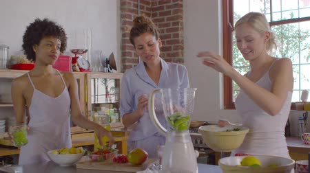 kitchen blender : Three female friends making smoothies in kitchen, shot on R3D Stock Footage