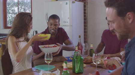 socialising : Six young adult friends passing food round a table, close up, shot on R3D Stock Footage