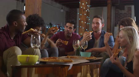 each other : Young adults sharing pizzas at a party at home, shot on R3D Stock Footage