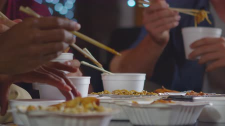 достигать : Adult friends sharing a Chinese take-away, close up mid section, shot on R3D