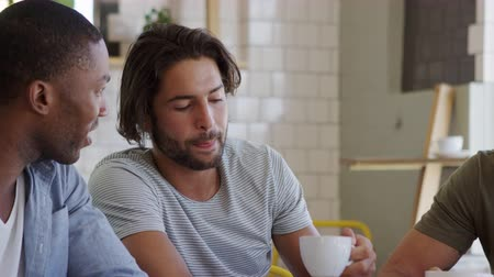 drinking coffee : Three Male Friends Meeting In Coffee Shop Shot In Slow Motion