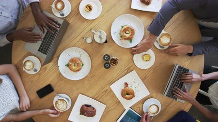 looking down : Overhead Shot Of Businesspeople Meeting Around Coffee Shop Table Stock Footage