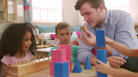 encouraging : Teacher And Pupils Using Wooden Shapes In Montessori School Stock Footage