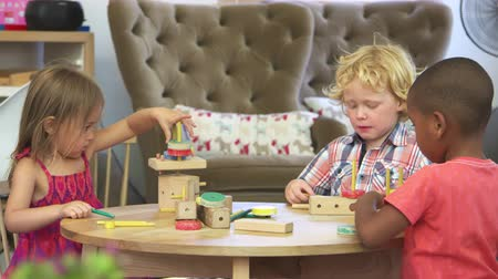 focus on foreground : Montessori School Pupils Work At Desk With Wooden Building Set Stock Footage