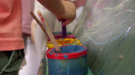 focus on foreground : Close Up Of Paint Pots On Easel During School Art Lesson