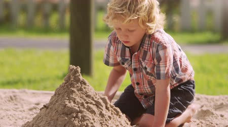 cova : Male Pupil At Montessori School Playing In Sand Pit At Breaktime