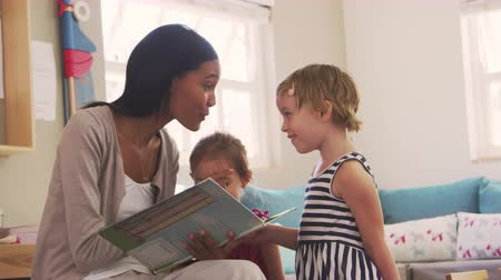 encouraging : Teacher At Montessori School Reading To Children At Story Time