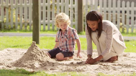 breaktime : Teacher At Montessori School Playing With Male Pupil In Sand Pit
