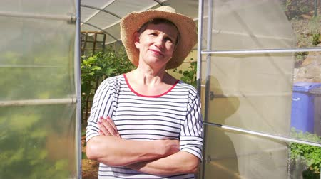 self sufficiency : Portrait Of Mature Female Gardener Outside Allotment Greenhouse