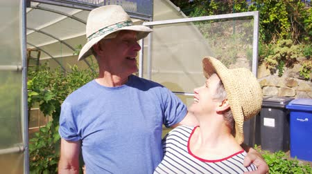 home grown : Portrait Of Senior Couple Outside Allotment Greenhouse Stock Footage