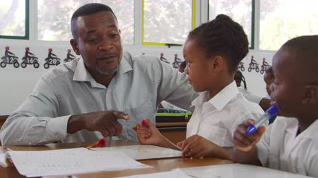 school children : Teacher helps elementary school kids at their desk in class Stock Footage