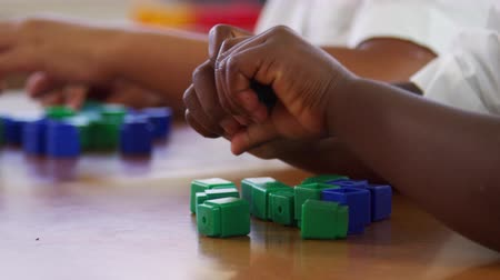 etnia africano : Elementary school kids hands playing with blocks, close up Stock Footage