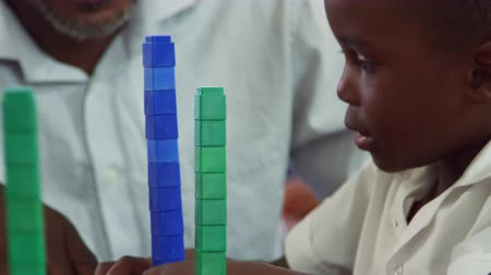 balanceamento : Teacher helping elementary school boy balancing blocks Stock Footage
