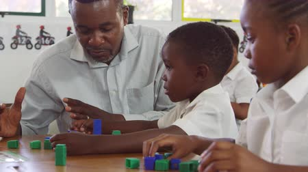 schoolkid : Teacher helping elementary school boy counting with blocks
