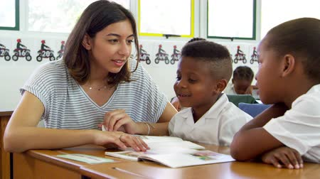 internar : Volunteer teacher helps young school kids in class, close up