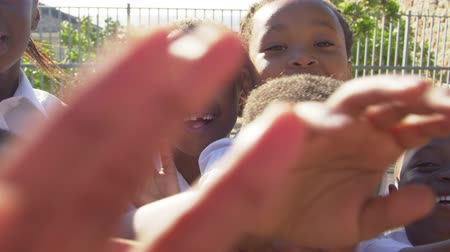 recess : Young school kids in playground wave to camera, slow motion Stock Footage