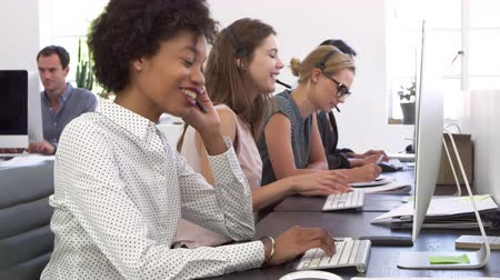 v řadě : A row of women using phone headsets in an open plan office