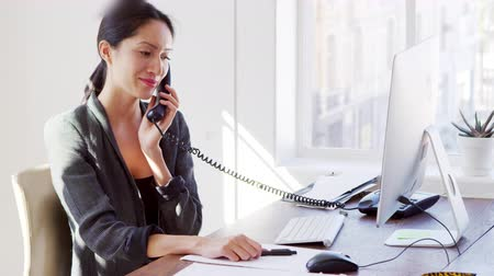 looking down : Young Asian woman on the phone smiling at her office desk
