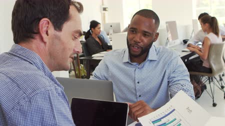 etnia africano : Two men discussing business in a busy office Stock Footage